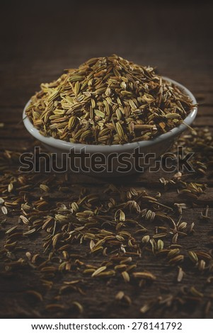 Fennel seeds in a small bowl on an old wooden table. - stock photo