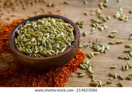 Fennel seeds in a small wooden bowl on an old wooden table. Other spices in the background.