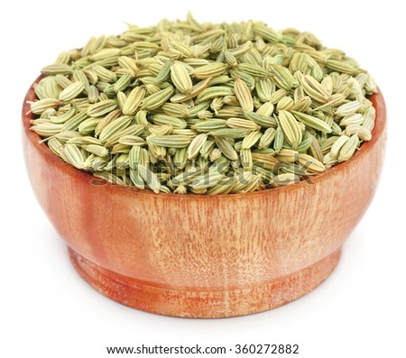 Fennel seeds in wooden pot over white background