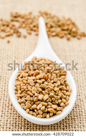 Fenugreek seeds in white spoon on sack background.