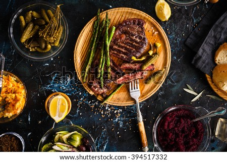 Fermented veggies and grilled meat concept. Sliced medium rare grilled beef barbecue Ribeye steak with chimichurri sauce, beet dip, red cabbage on cutting board on a dark food background. - stock photo