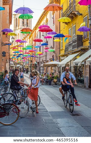 Ferrara, Italy - July 20, 2016. Cyclists crossing Via Giuseppe Mazzini of Ferrara covered with colored umbrellas and tower of San Giorgio cathedral in background. Emilia-Romagna. Italy.