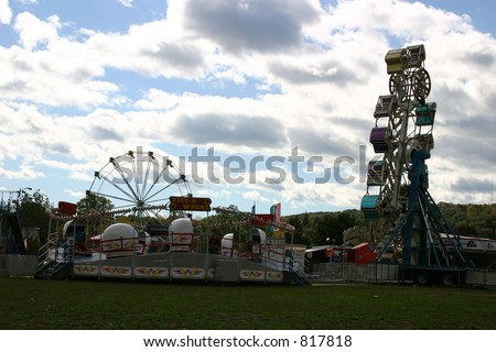 Ferris Wheel and tilt a whirl at a city carnival. - stock photo