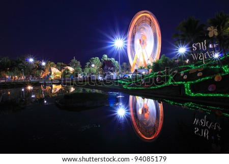 Ferris wheel at night view with water reflection
