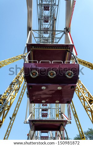 Ferris wheel cabin close-up against clear blue sky - stock photo