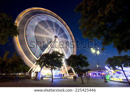 Ferris Wheel in motion during Fair. - stock photo