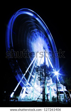 Ferris wheel in motion in a night time background - stock photo