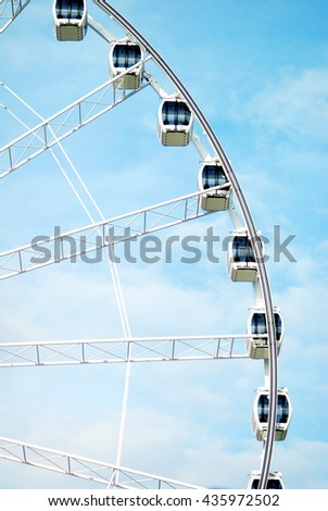 Ferris wheel on blue sky with clouds - stock photo