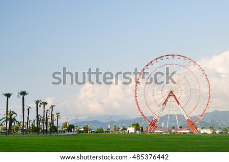 ferris wheel on green field, mountains, palms and blue sky with light clouds on the promenade of Batumi, Georgia