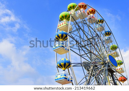 Ferris wheel on the background of blue sky with cloud - stock photo