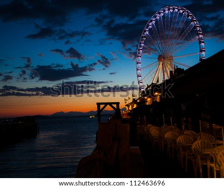 Ferris wheel on the water at sunset - stock photo