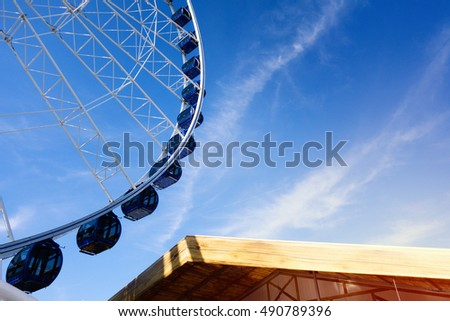 Ferris wheel over blue sky. Sunny day