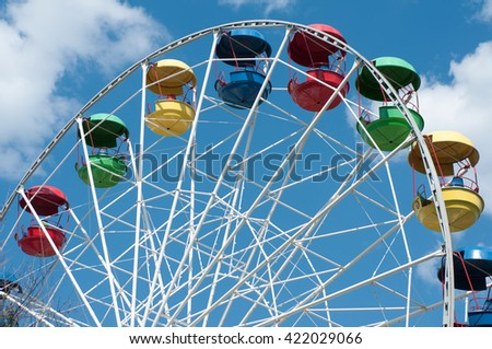 Ferris wheel with baskets of different colors in the park on blue sky background
