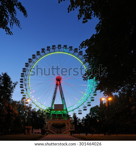 Ferris wheel with multicolored illumination with dark trees in the foreground against the blue night sky. - stock photo