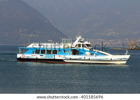 Ferry boat at Lake Iseo (Sebino Lake) tourist modern boat shipping company pier approaching. Iseo Lombardy Italy. March 26, 2016