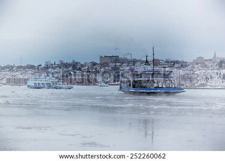 Ferry boat in ice on St-Lawrence river between Quebec and Levis in Canada during winter season. - stock photo