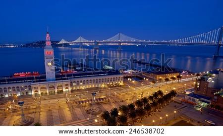 Ferry Building and Bay Bridge illuminated at night in San Francisco, California - stock photo