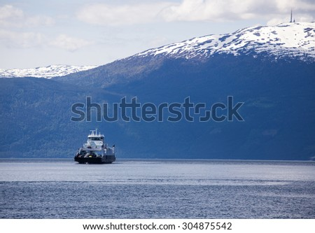ferry crossing a norwegian fjord with mountains at the background - stock photo