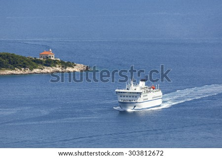 Ferry in Adriatic is coming in the port near lighthouse on the island, Croatia