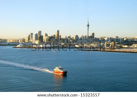 ferry passing by Auckland Harbor in sunrise light, New Zealand - stock photo