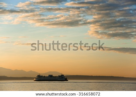 Ferryboat at Sunset. A Washington state ferry crosses Elliott Bay to Bainbridge Island during the commute hour during  lovely sunset and dramatic sky.