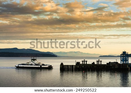 """Ferryboat Docking. A ferryboat takes passengers to Lummi Island, Washington in the San Juan Islands of Puget Sound. The """"Whatcom Chief"""" has been serving the island for 50 years. - stock photo"""