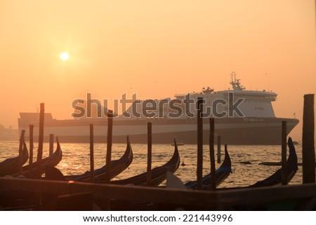 Ferryboat sailing near venetian gondolas at sunrise - stock photo