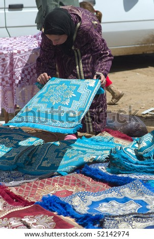 FES - APRIL 16: Arabic women at a market (souk) with carpets in a village near Fes in Morocco April 16, 2010 Fes, Morocco. - stock photo