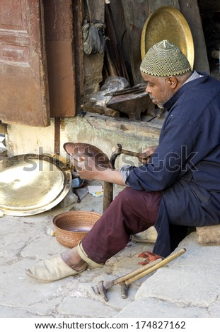 FES,MOROCCO - FEBRUARY 05:Morroccan craftsmen make and sell pots and dishes in metal in the souk of Fes on February 5,2013.