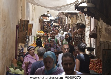 FES, MOROCCO - JULY 27: People on a street market on July 27, 2010 in Fes, Morocco. Fes center is listed in UNESCO and it is the largest preserved medieval city in the world. Also it's one big market. - stock photo