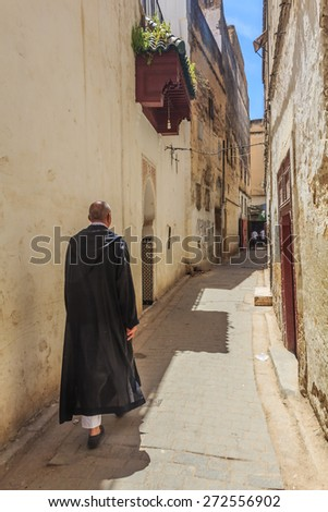 Fes, Morocco - May 11, 2013: Man in djellaba, berber clothing walking down a street in Fes Medina in Morocco3: Man in djellaba, berber clothing walking down a narrow street in Fes Medina in Morocco - stock photo