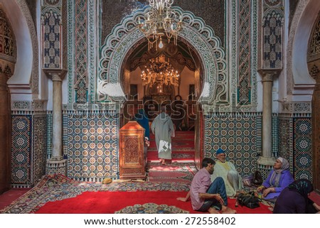Fes, Morocco - May 11, 2013: People sitting by the entrance to a mosque, decorated with ornate mosaic and arabesque carvings - stock photo