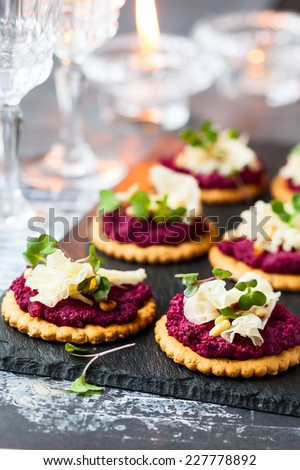 Festive appetizer: crackers with beet pesto and cheese - stock photo