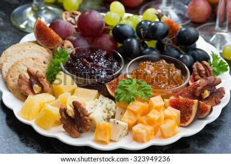 festive appetizers - cheeses, fruits and jams on plate, closeup, horizontal - stock photo