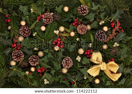 Festive background of holly, mistletoe and ivy leaf springs with blue spruce, pine cones, gold bow and bauble arrangement. - stock photo