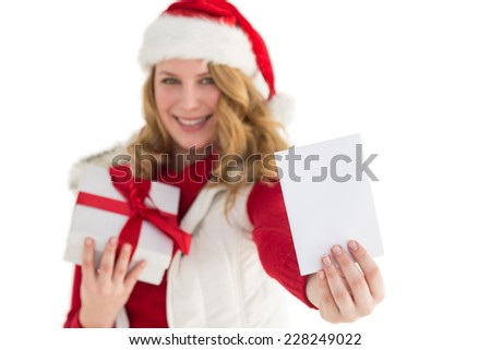 Festive blonde holding christmas gift and showing a card on white background
