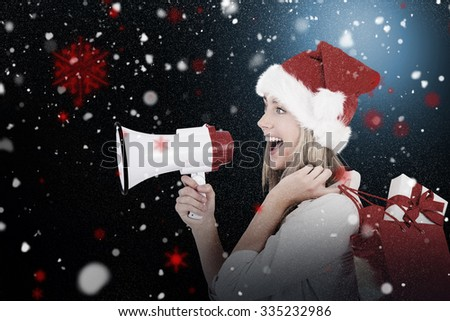 Festive blonde holding megaphone and bags against snow - stock photo