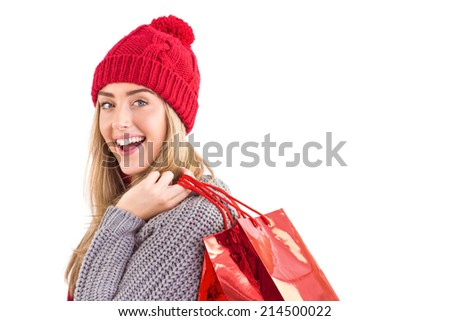 Festive blonde holding shopping bags on white background - stock photo