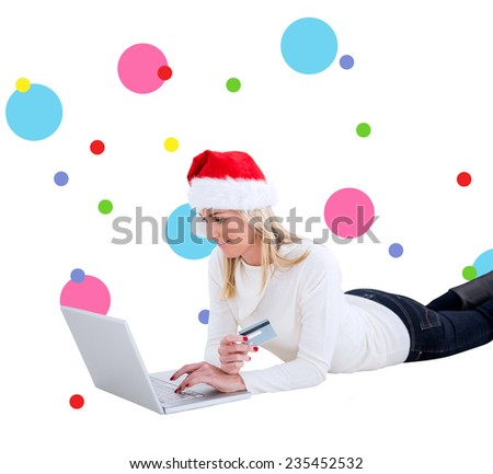 Festive blonde shopping online with laptop against dot pattern - stock photo