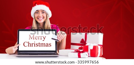 Festive blonde shopping online with laptop against red snowflake background - stock photo