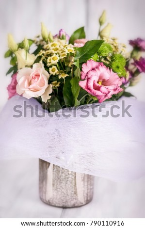 Festive bouquet of various flowers in a vase on a white wooden background