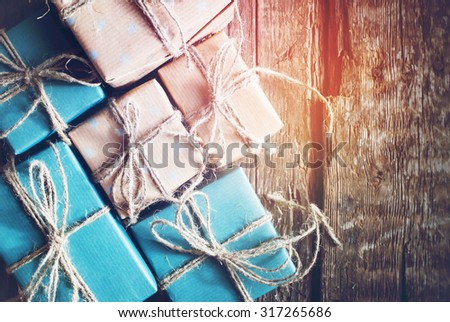 Festive Boxes are Packed into a Brown Paper with Linen Cord on Wooden Table. Toned with Light Shine Effect - stock photo