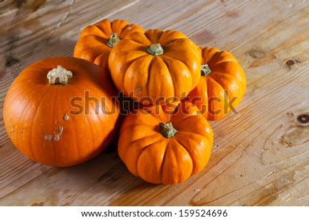 Festive bright orange pumpkins against wooden background. Copy space.