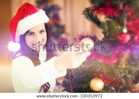 Festive brunette decorating a christmas tree at home in the living room - stock photo