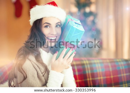 Festive brunette holding gift at christmas at home in the living room - stock photo