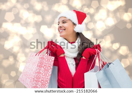 Festive brunette holding shopping bags against light glowing dots design pattern