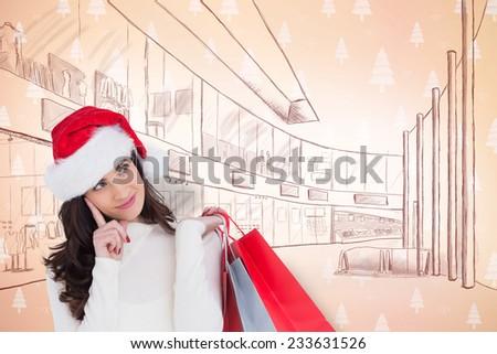 Festive brunette holding shopping bags and thinking against orange tree pattern - stock photo