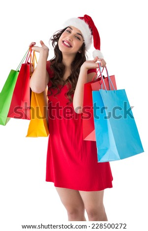 Festive brunette holding shopping bags on white background