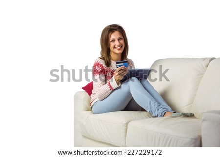 Festive brunette shopping online with tablet pc at home in the living room - stock photo