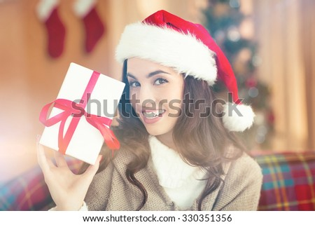 Festive brunette showing gift at christmas at home in the living room - stock photo